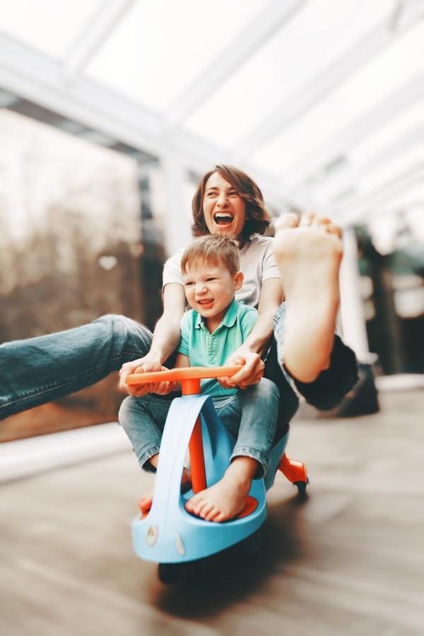 Mamá en un triciclo jugando con su hijo