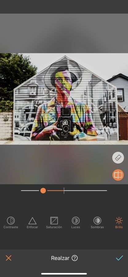 Arte urbano de un hombre sosteniendo una cámara, pintado en la fachada de una casa.