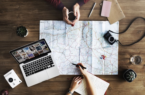 travel flat lay with laptop, camera and map