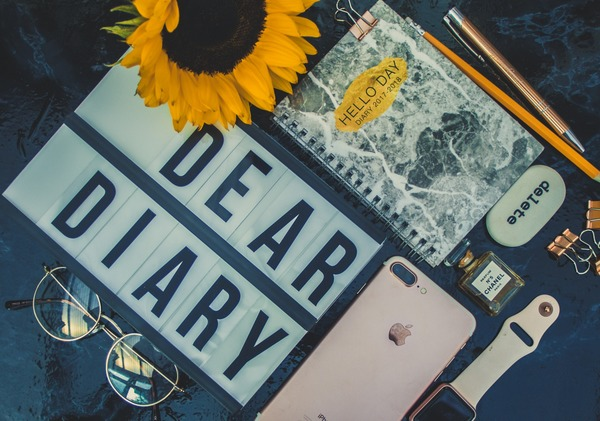 flat lay of sign, phone, watch, notebook and sunflower