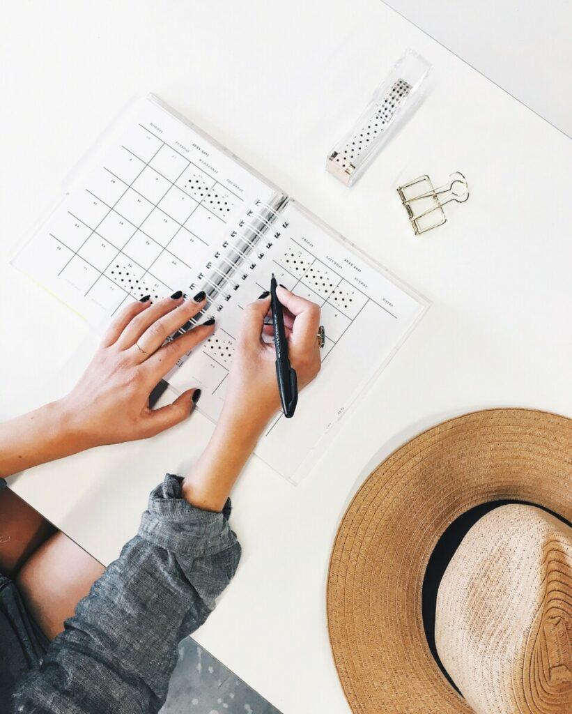 Uma imagem de uma mulher preenchendo um planner em cima de uma mesa branca, junto com um chapéu de palha
