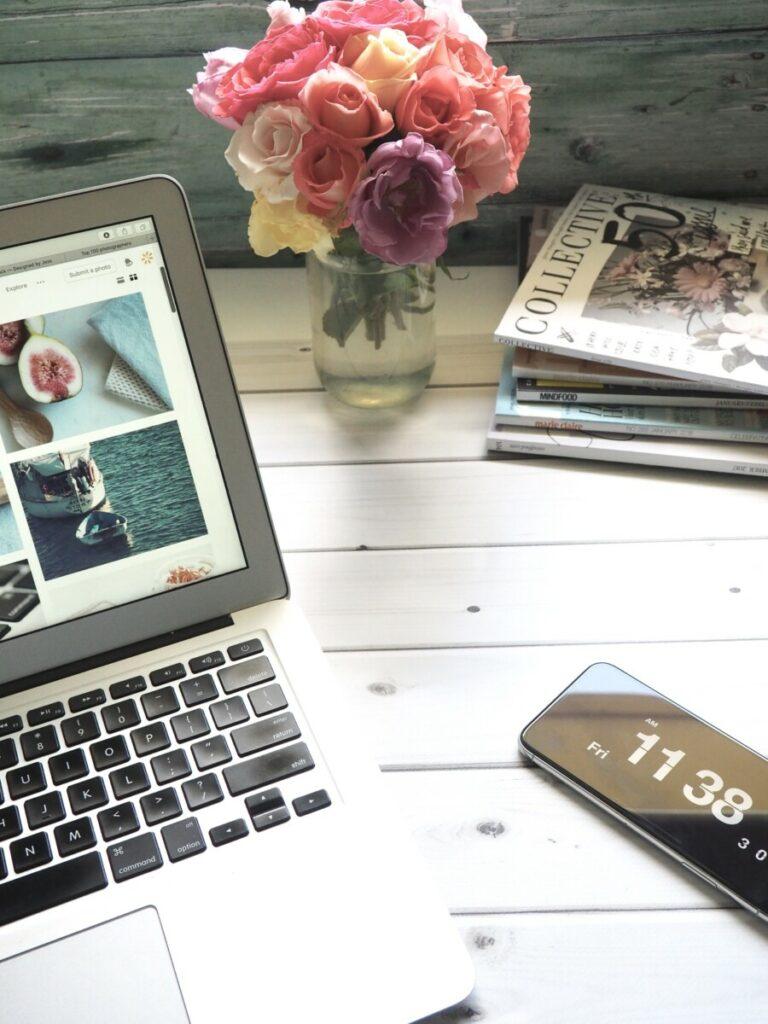 Uma imagem de um notebook aberto em um site de imagens, revistas e um jarro de flores junto com um celular em cima de uma mesa