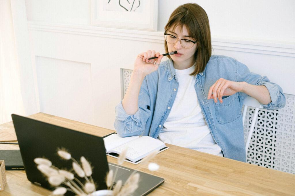 Uma mulher branca de cabelo curto, lendo um livro em frente a um computador