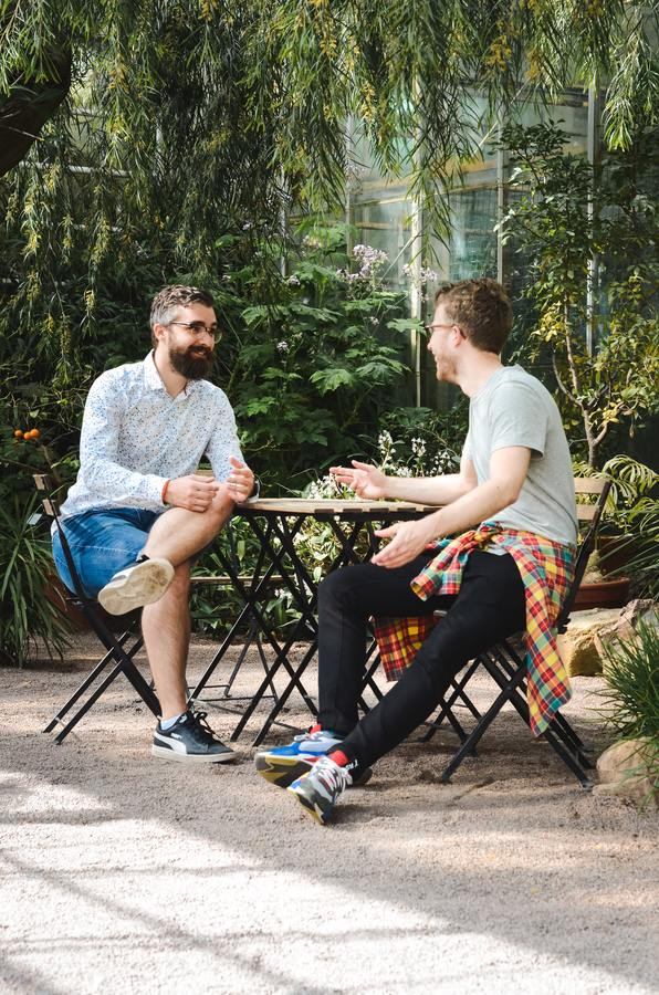 two men sitting at a table in a garden