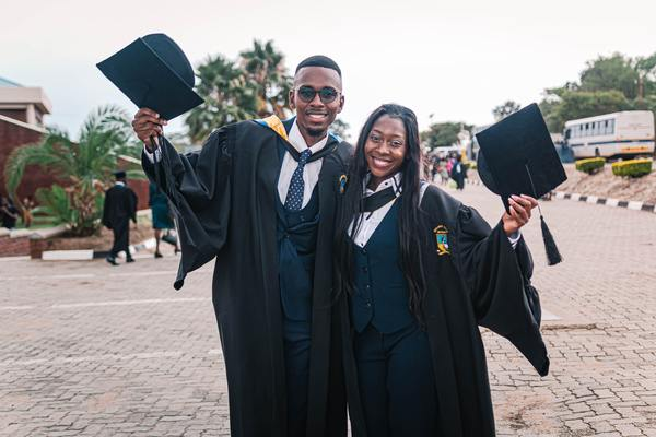 two graduates celebrating in cap and gown