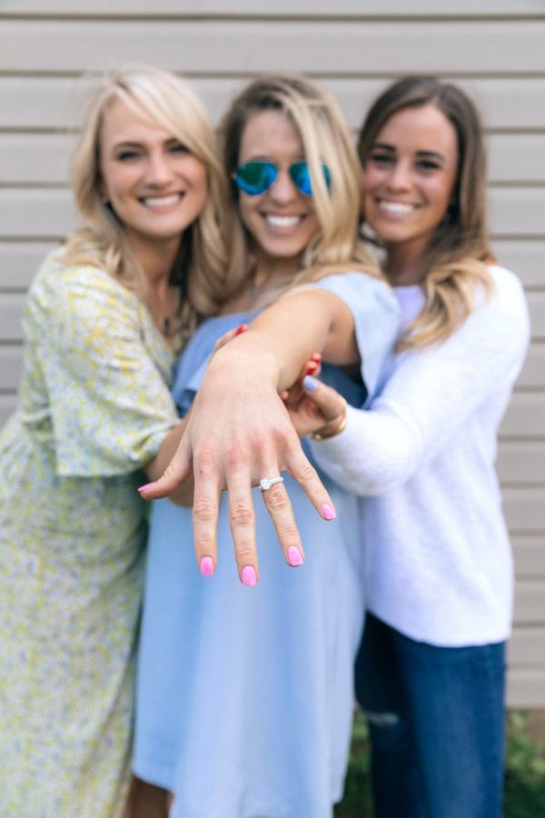 woman showing off her engagement ring while two friends hug her