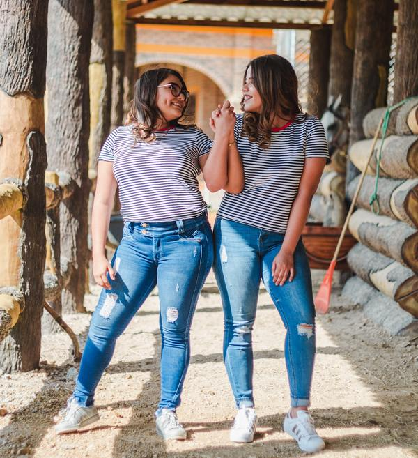 two women wearing jeans and striped t-shirts holding hands