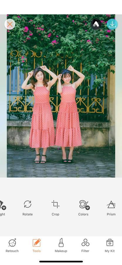 two women standing on the sidewalk wearing red polka dot dresses