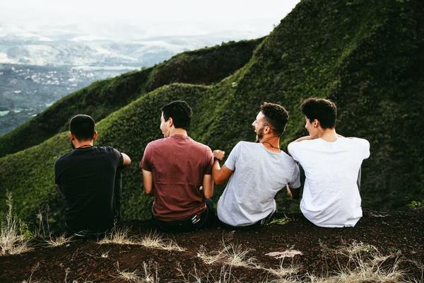 four men sitting on top of a mountain