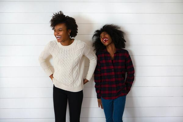 two women standing in front of a white wall laughing