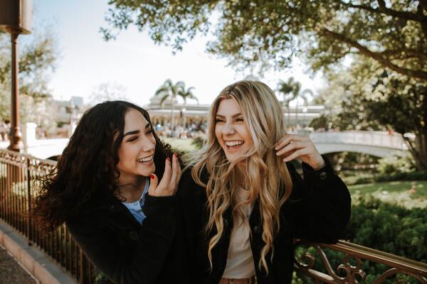 two women laughing outdoors