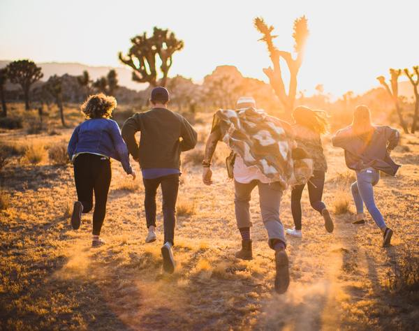 a group of people running in the desert