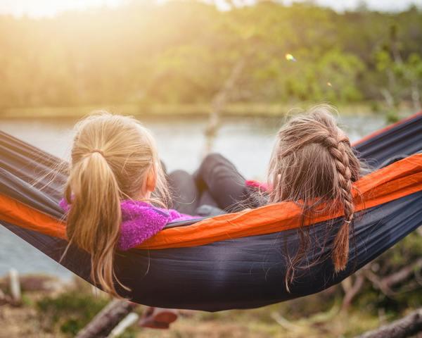 two women in a hammock facing a lake