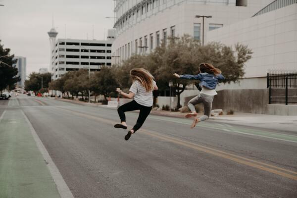 two women jumping in an empty street