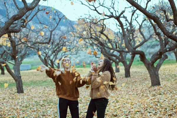 two women playing with fall leaves