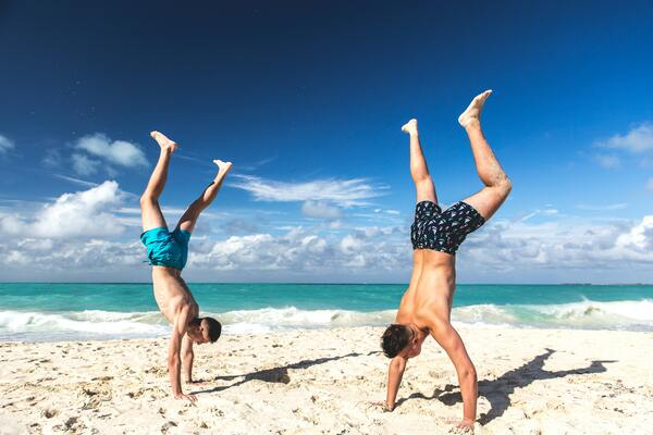 two men doing hand stands on the beach