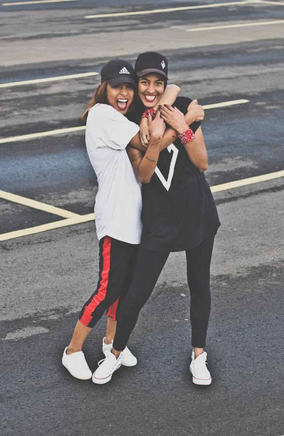 two friends in leggings and t-shirts hugging in the street
