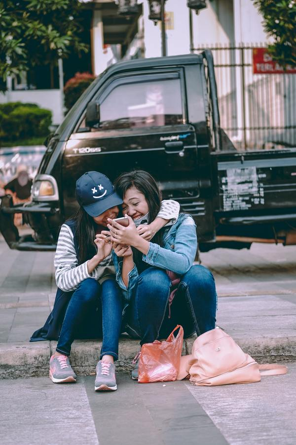 two girls seated on the sidewalk hugging