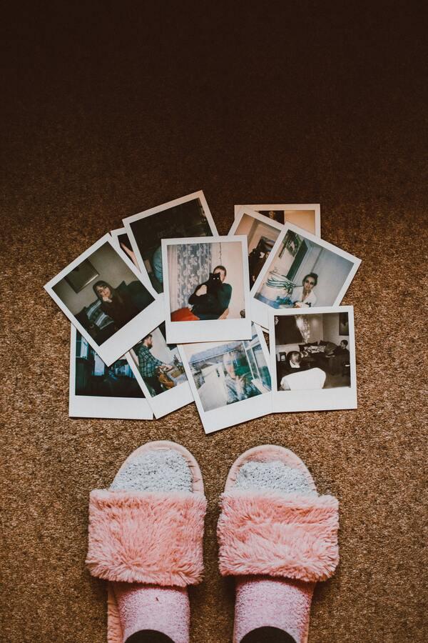 fotografías instantáneas estilo polaroid en el piso junto a unos pies