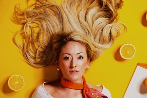 mujer acostada en un fondo amarillo con naranjas cortadas al rededor de ella