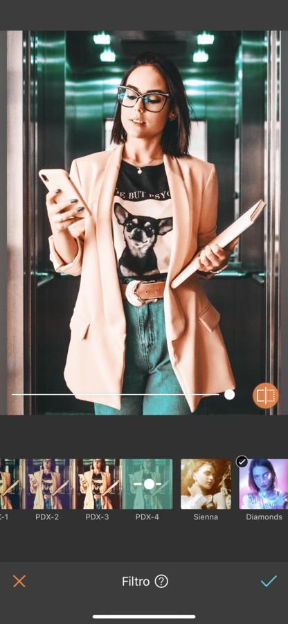 mujer trabajadora, con blazer rosa, playera con un chihuahua y su celular en la mano