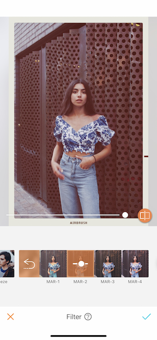 faded photo Kim Kardashian lookalike in blue jeans and floral top standing in front of metal wall