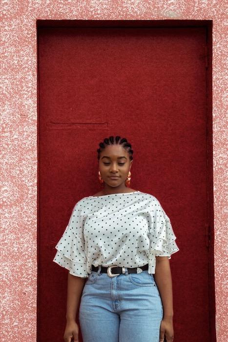 woman standing in front of a red door