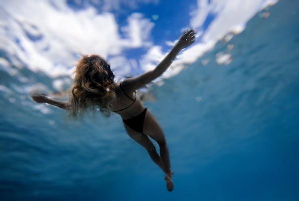 woman in black bikini floating in clear water