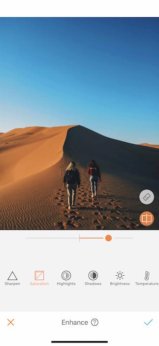 two women walking on a sand dune