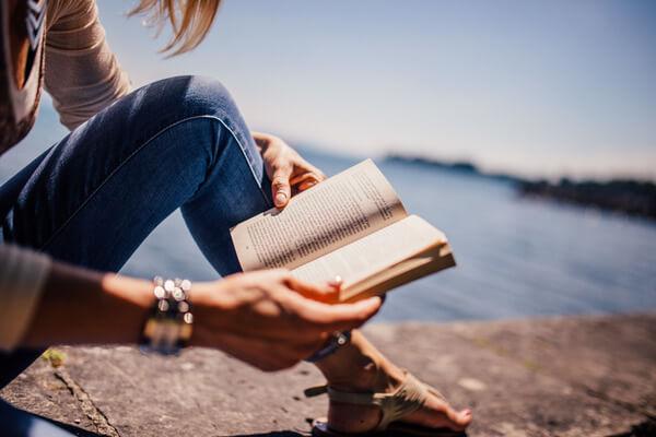 persona leyendo un libro en la orilla del mar