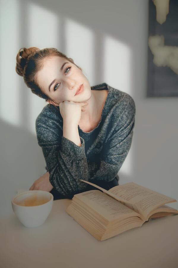 Mujer con un libro abierto sobre la mesa y una taza de café.