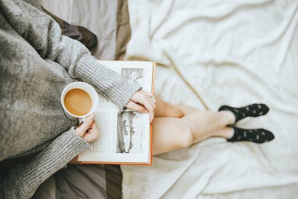 Foto tomada desde arriba de una persona con un libro apoyado sobre sus piernas y una taza de café.