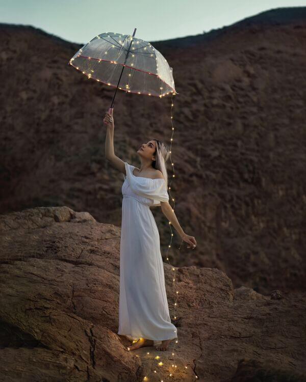 mujer con vestido blanco, paraguas y luces