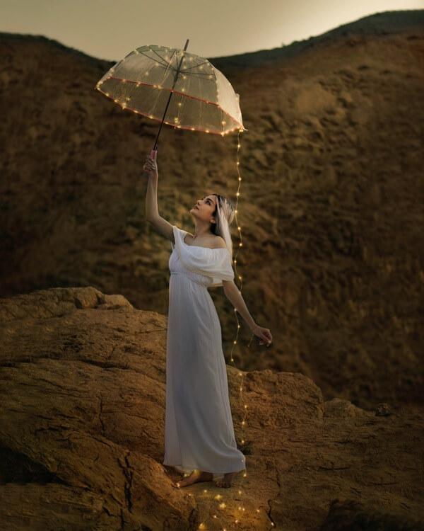 mujer con vestido blanco y paraguas transparente