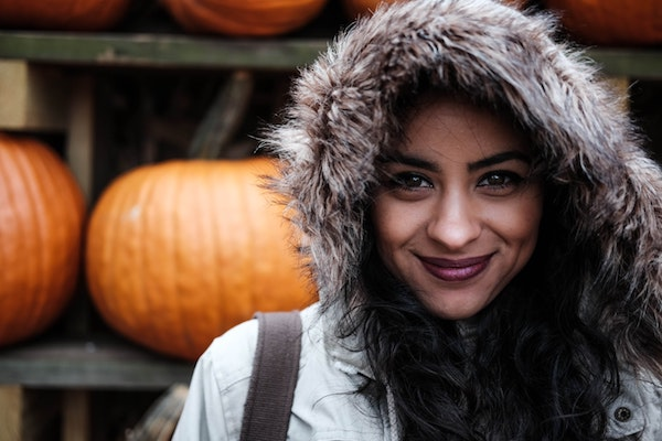 smiling woman wearing hooded jacket stands in front of pumpkins