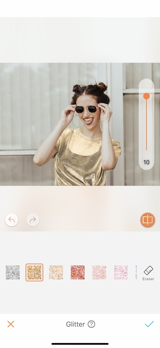 woman in a gold top holding sunglasses to her face