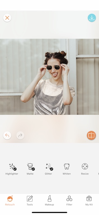 woman in a silver top holding sunglasses to her face