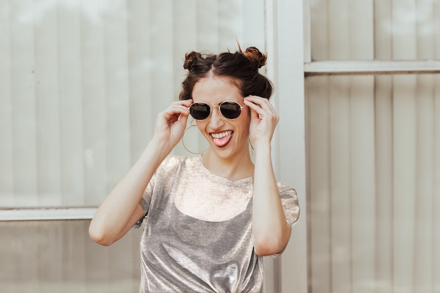 laughing woman holding sunglasses up to her face against light background