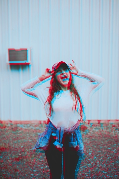 blurry photo of woman laughing wearing a white shirt and cap