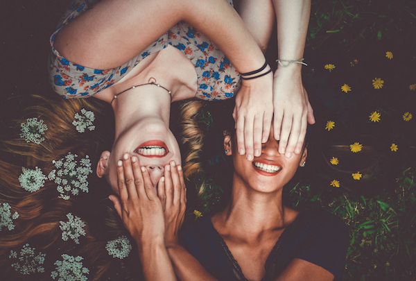 women covering each other's eyes and smiling