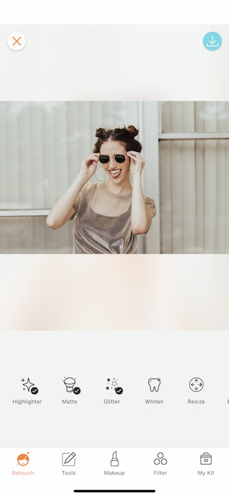 laughing woman wearing sunglasses in front of light background