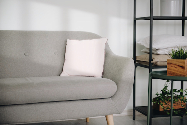 pink pillow on grey couch