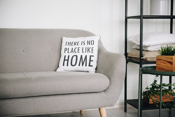 white pillow with black writing on grey couch