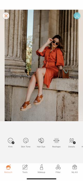 woman wearing orange dress posing in front of pillars