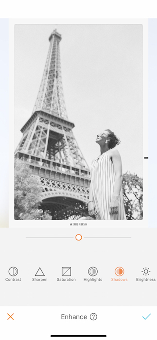black and white photo of white woman standing in front of the Eiffel Tower