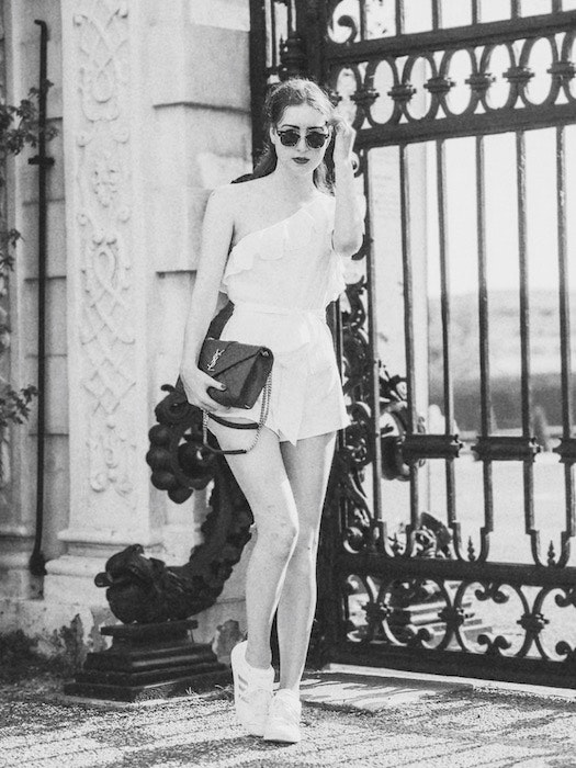black and white photo of a woman in a white romper standing in front of a black gate