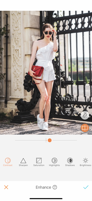 woman in a white romper holding a red purse in front of a black gate