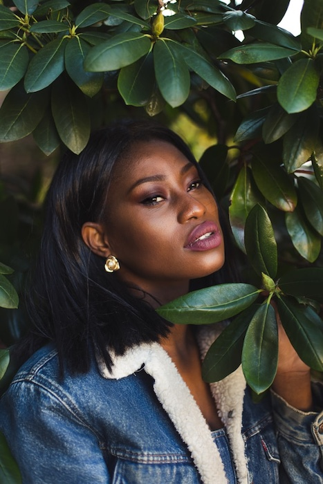 black woman in denim jacket surrounded by green leaves