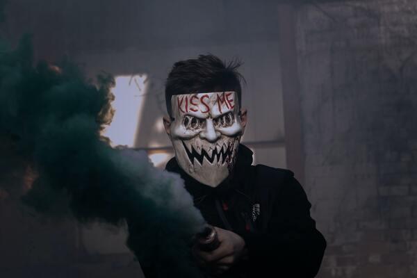 foto de um homem com uma máscara escrita Kiss Me