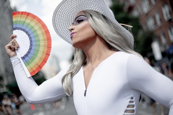 foto de um homem em drag com leque de arco-irís